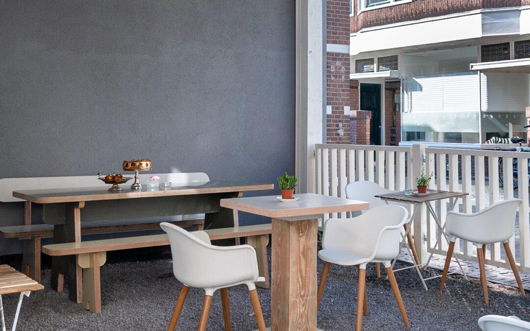 Overdekt terras. Klein houten tafels op maat gemaakt. Combinatie van verschillende houtsoorten. Balustrade handgemaakt